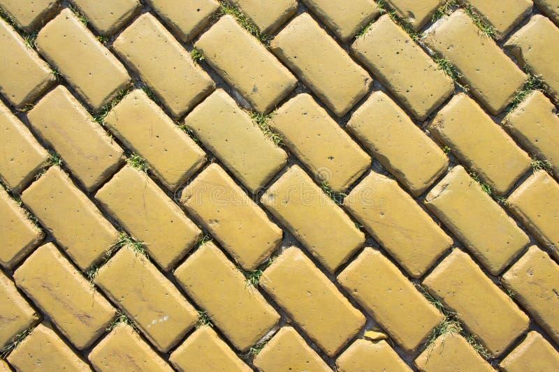 Żółta ceglana droga kiełkował zieloną trawą pod jaskrawym lata słońcem zdjęcia royalty free