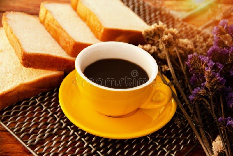 Żółta ceramiczna filiżanka z czarną kawą stawiającą obok pokrojonego chleba, rocznik i sztuka, projektujemy, ciepły lekki brzmien obrazy royalty free