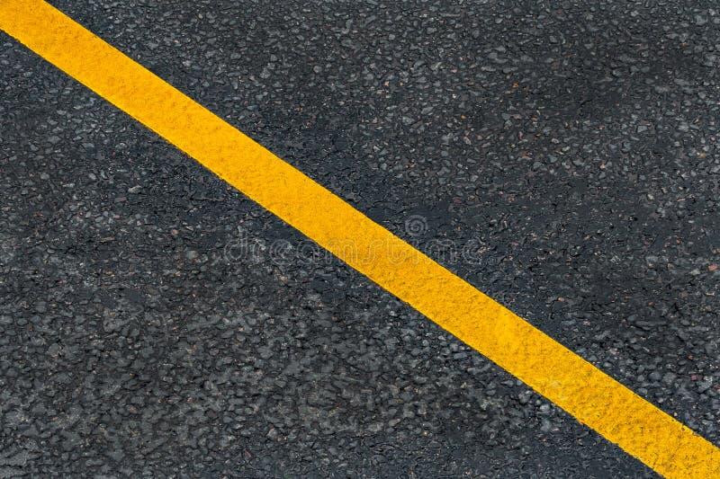 Żółta diagonalna ocechowanie linia na asfaltowej drodze obrazy stock
