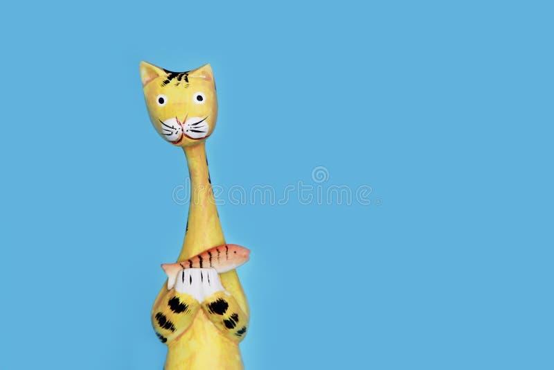 Żółta drewniana kot pamiątka trzyma pomarańczowej ryby w swój łapach zdjęcie royalty free