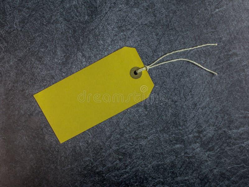 Żółta etykietka z sznurkiem na ciemnym łupkowym tle fotografia stock