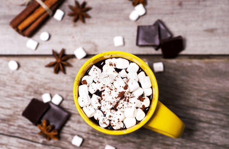 Żółta filiżanka kakao z marshmallows, gwiazdowym anyżem i cynamonem na drewnianym tle, zdjęcia stock