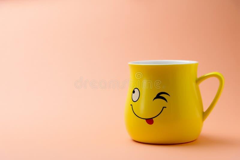 Żółta filiżanka z mrugać uśmiechem na barwionym tle zdjęcie royalty free