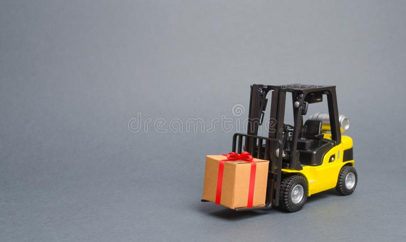 Żółta forklift ciężarówka niesie prezent z czerwonym łękiem Zakup i dostawa teraźniejszość handel detaliczny, pomija i rywalizuje zdjęcie stock