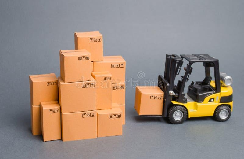 Żółta Forklift ciężarówka przynosi pudełko sterta pudełka Przemys? i produkcja magazyny i transport podwyżka ekonomiczna zdjęcia royalty free