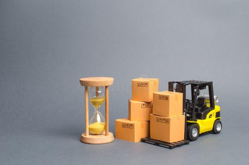 Żółta Forklift ciężarówka z kartonami i piaska hourglass Ekspresowej dostawy poj?cie Optymalizacja logistyka i dostawa zdjęcia stock