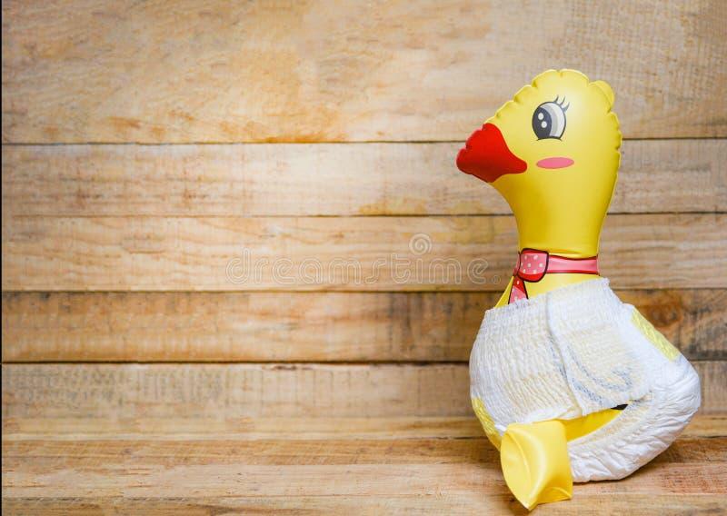 Żółta gumowa kaczka dla pływać i dziecka dziecka skąpania odzieży zabawkarska pieluszka na drewnianym obraz stock