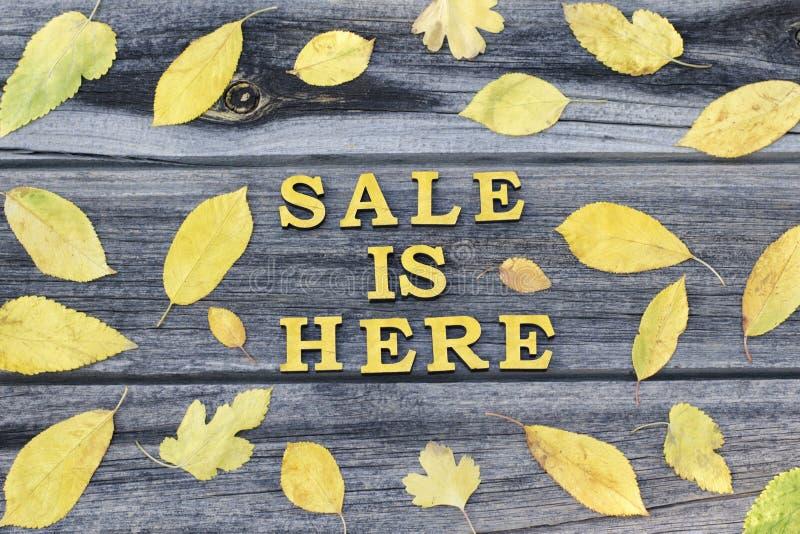 Żółta inskrypcja Sprzedaż jest tutaj pisze list drewnianego Rama yello fotografia stock