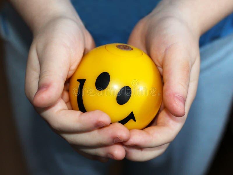 Żółta piłka z Smiley twarzą wewnątrz w dziecka ` s rękach obraz stock