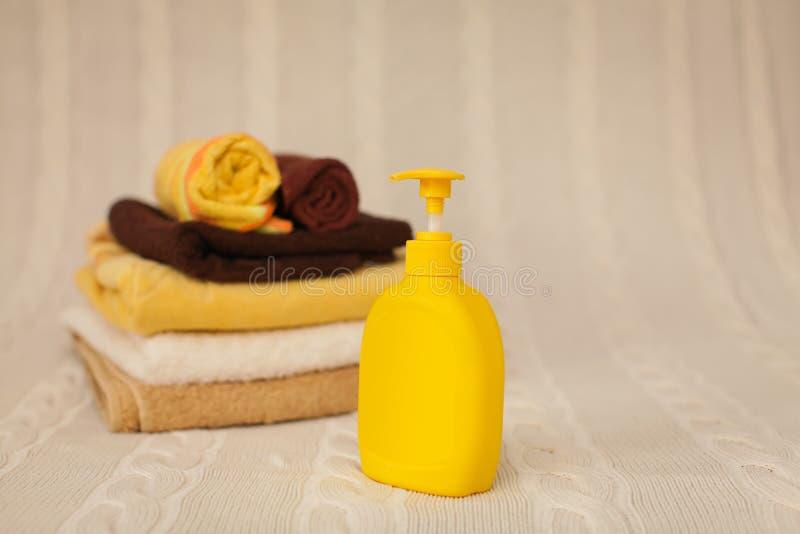 Żółta plastikowa aptekarka z ciekłym mydłem i sterta brązów ręczniki na beżowym dywaniku w selekcyjnej ostrości zdjęcia royalty free