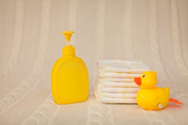 Żółta plastikowa aptekarka z ciekłym mydłem i sterta brązów ręczniki na beżowym dywaniku w selekcyjnej ostrości obrazy royalty free