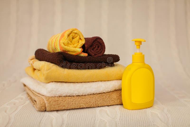 Żółta plastikowa aptekarka z ciekłym mydłem i sterta brązów ręczniki na beżowym dywaniku w selekcyjnej ostrości obraz stock