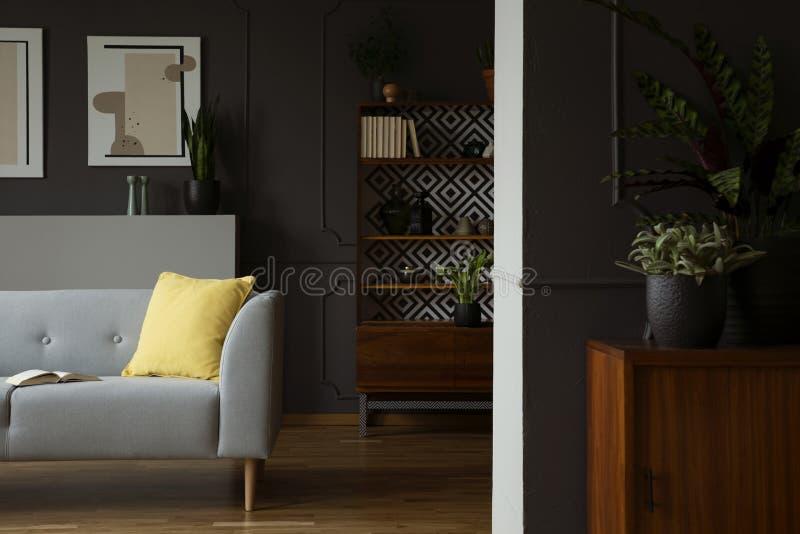 Żółta poduszka na popielatej kozetce w retro żywym izbowym wnętrzu z plakatami i roślinami Istna fotografia obrazy stock