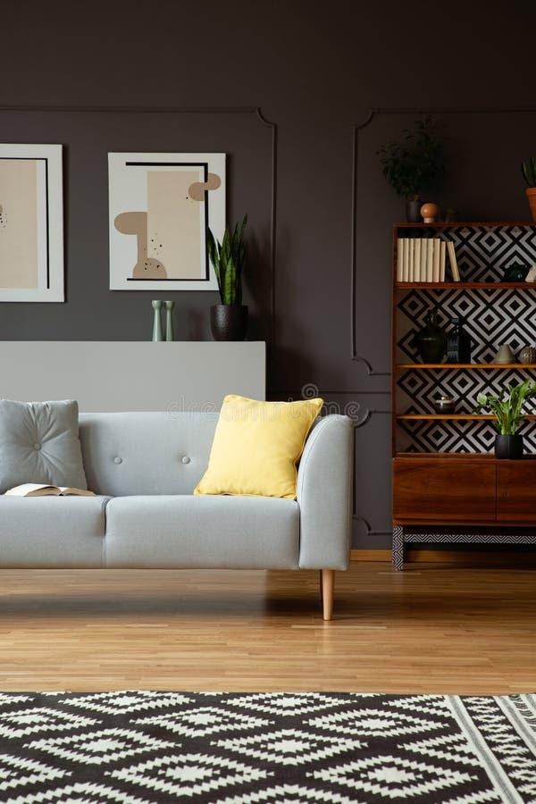 Żółta poduszka na popielatej leżance w retro żywym izbowym wnętrzu z wzorzystym dywanem i plakatami Istna fotografia zdjęcia royalty free