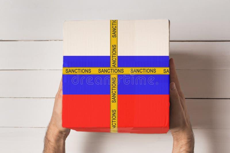 Żółta taśma z napisem Sankcje na pudełku z flagą Rosji w rękach mężczyzn. Biała tabela w widoku u góry obrazy stock