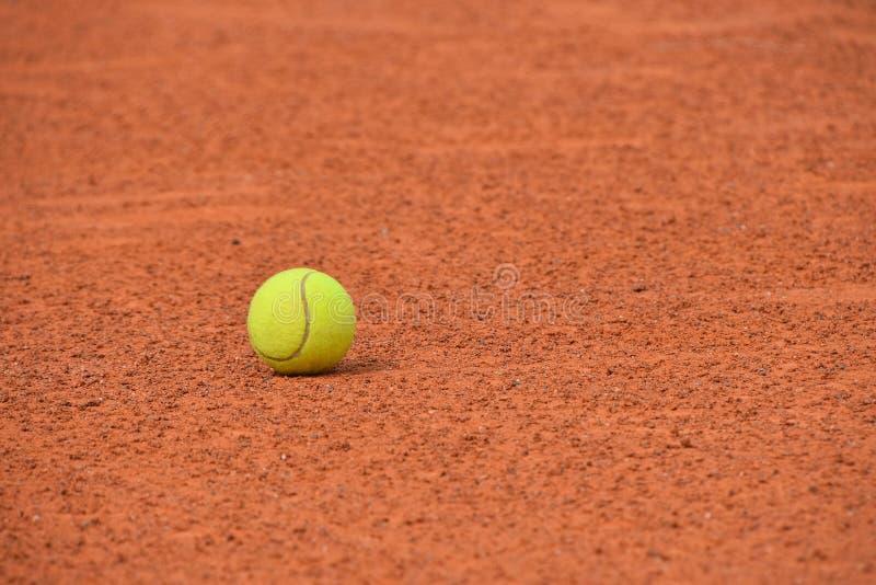 Żółta tenisowa piłka na czerwonej gliny ziemi sądzie zdjęcie royalty free