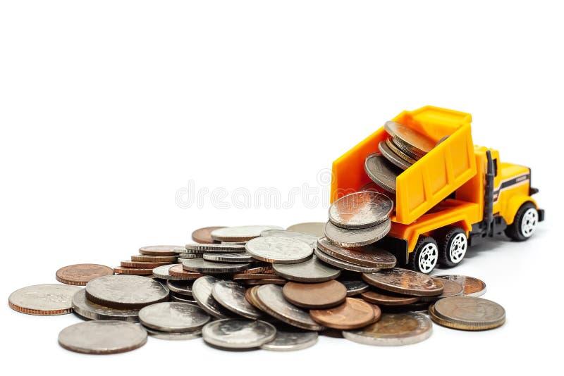 Żółta zabawkarska usyp ciężarówka z stosem monety na białym tle fotografia royalty free