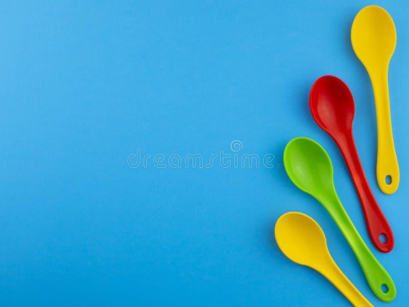Żółte czerwieni i zieleni plastikowe łyżki na błękitnym tle z kopii przestrzenią dla teksta zdjęcie stock