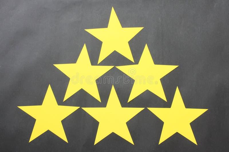 Żółte gwiazdy umieszczają na czarnym tle dla biznesowych pomysłów fotografia royalty free