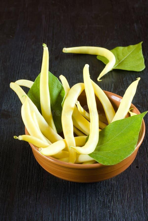Żółte i fasolowe strÄ…ki haricot w miseczce glinowej na drewnianym stole zdjęcie royalty free