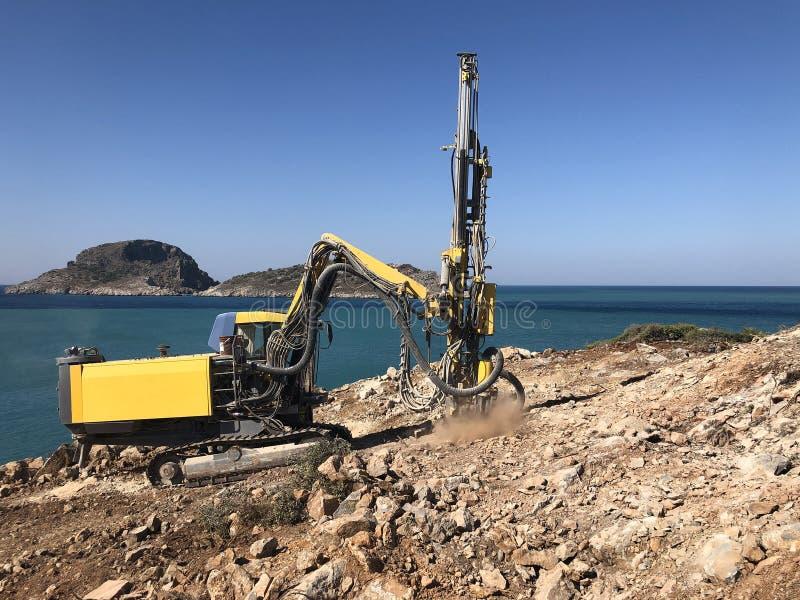 Żółte maszyny to otwory wiertnicze na szczycie skalistego klifu morskiego podczas wierceń przy użyciu dziur zdjęcie royalty free