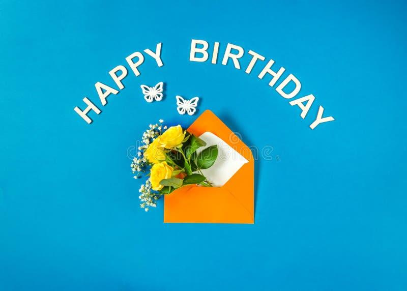 Żółte róże i łyszczec w kopercie i motylach na cyan tle urodzinowego czarny koloru szcz??liwy teksta biel Odg?rny widok, mieszkan zdjęcie stock