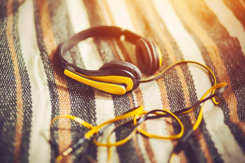 Żółte słuchawki z mikrofonem leżą na miękkim wełnianym kocu, oświetlonym ciepłym światłem słonecznym obraz royalty free