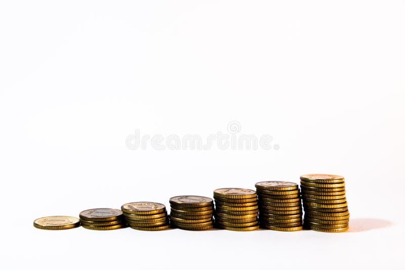 Żółte złote monety ułożone w rosnące pale, stanowiące stały wzrost przychodów odizolowanych na białym tle z przestrzenią kopiową obrazy royalty free