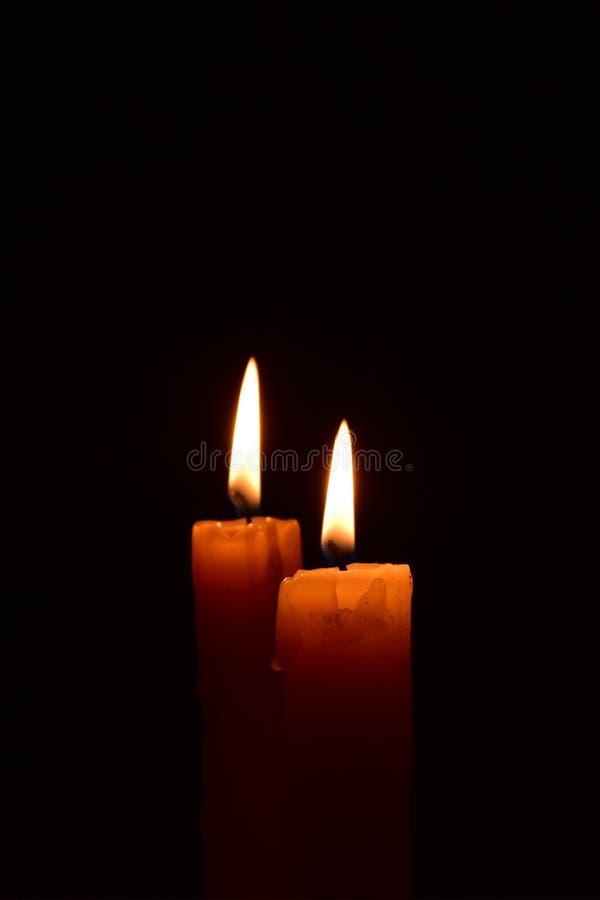 Żółtego światła świeczka pali jaskrawy w czarnym tle fotografia royalty free