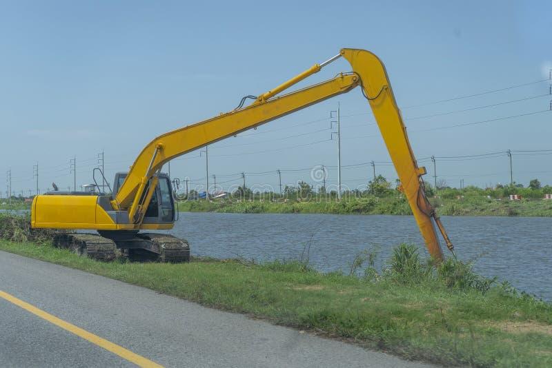 Żółtego backhoe pracujący brzeg rzeki na poboczu i obrazy stock