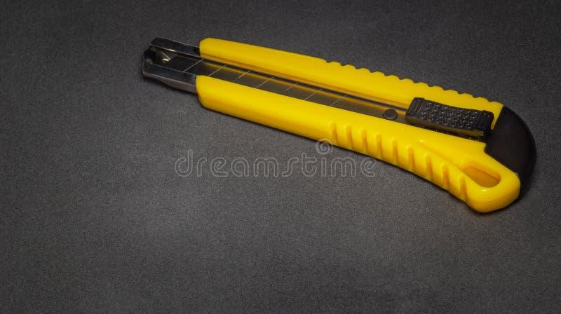 Żółtego materiały biurowy nóż na zmroku - szarość ukazują się zdjęcia stock