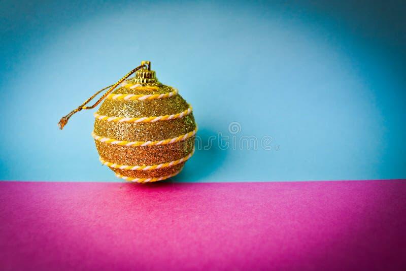 Żółtego złota małego round xmas świąteczna Bożenarodzeniowa piłka, boże narodzenie zabawka gipsująca błyska na różowym purpurowym fotografia stock