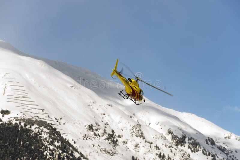 Żółty śmigłowcowy latający w powietrzu nad miasteczkiem w Engadin St Moritz Szwajcaria w alps dla zwiedzać w winte zdjęcie royalty free