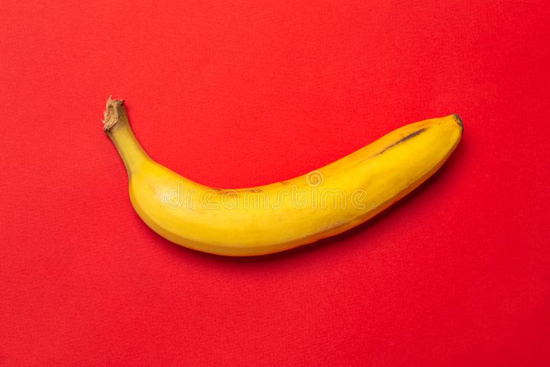 Żółty świeży dojrzały organicznie banan na czerwonym tle Nowożytny minimalny karmowy nadrealizmu pomysł dla projekta obrazy royalty free