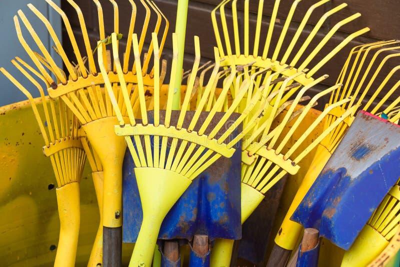 Żółty świntuch i łopaty dla ogrodowego praca stojaka pionowo w jaskrawej kolor żółty baryłce zdjęcia royalty free