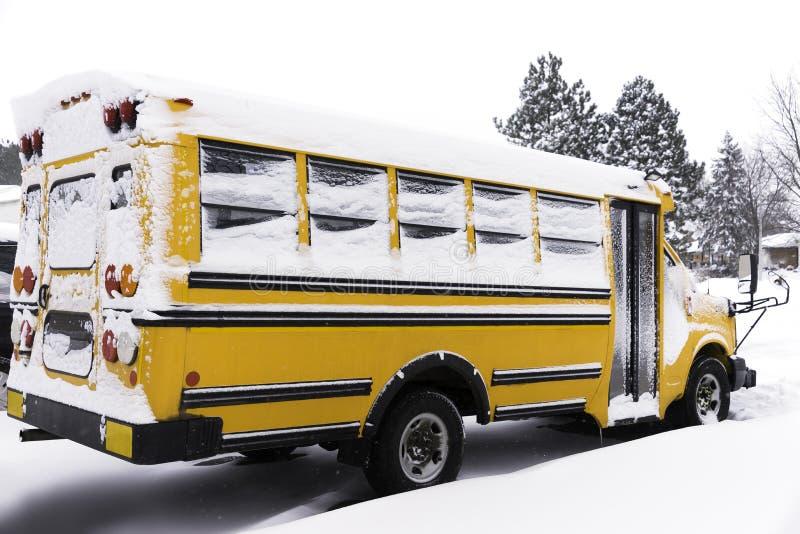 Żółty autobus szkolny zakrywający z śniegiem parkującym w mieszkaniowym neig zdjęcia royalty free