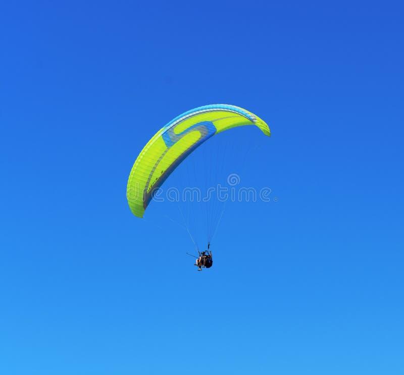 Żółty błękitny paraglider na niebieskim niebie zdjęcie stock