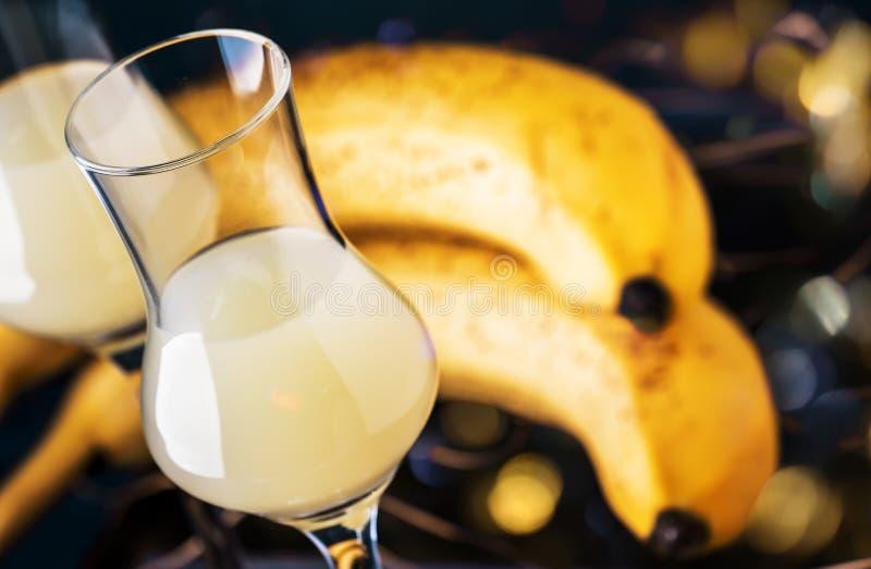 Żółty Bananowy ajerkoniak w strzałów szkłach i świeżych dojrzałych bananach na stole na zmroku - błękitny tło zdjęcia royalty free