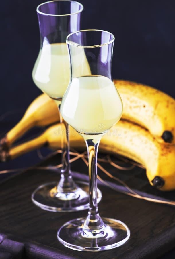Żółty Bananowy ajerkoniak w strzałów szkłach i świeżych dojrzałych bananach na stole na zmroku - błękitny tło zdjęcie stock