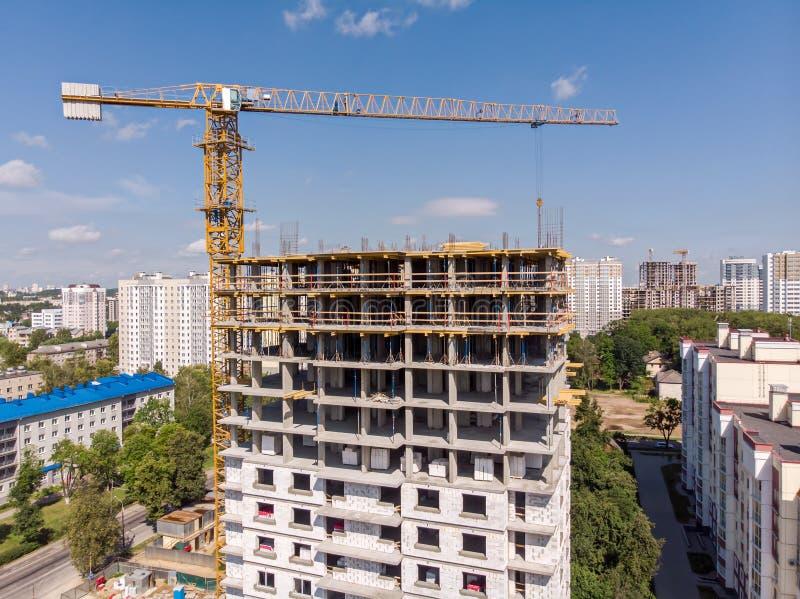 Żółty basztowy żuraw i budować w budowie widok z lotu ptaka zdjęcie stock