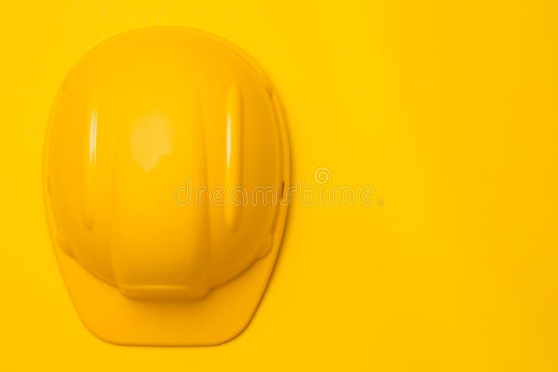 Żółty budowa hełm na żółtym tle, kierownicza ochrona, pojęcie, odgórny widok zdjęcie stock