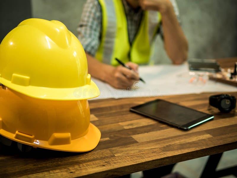 Żółty ciężki zbawczego hełma kapelusz dla zbawczego projekta robociarz jak inżyniera lub pracownik, W biurze, zbawczy pojęcie obrazy stock