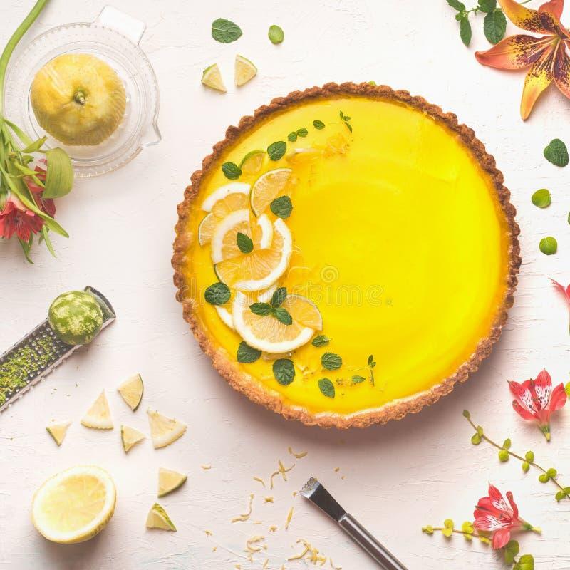 Żółty cytryny tarta nakrywający z świeżymi cytryny i wapna plasterkami na bielu zgłasza tło z cytrusów składnikami i kwiatami, od obrazy royalty free