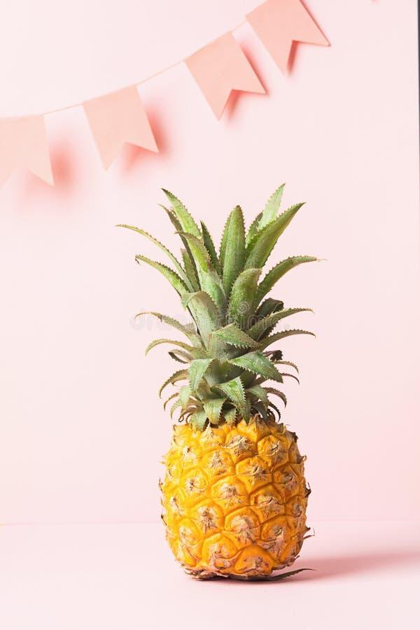 Żółty dojrzały ananas na delikatnym różowym tle z świątecznymi flagami minimalista ?wi?teczny poj?cie kosmos kopii obraz stock