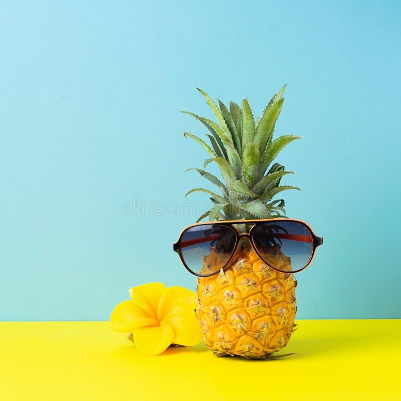 Żółty dojrzały ananas w okularach przeciwsłonecznych na żółtym błękitnym tle ?mieszna twarz od tropikalnej owoc Poj?cie obraz stock
