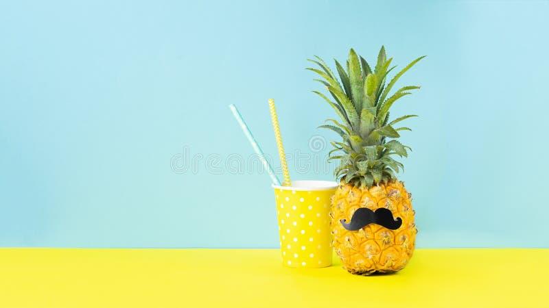 Żółty dojrzały ananas z czarnym wąsy szkłem dla napoju na żółtym błękitnym tle ?mieszny kaganiec tropikalna owoc zdjęcia stock