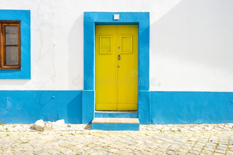 Żółty drzwi w tradycyjnym portuguese domu malował na błękitnym i białym fotografia stock