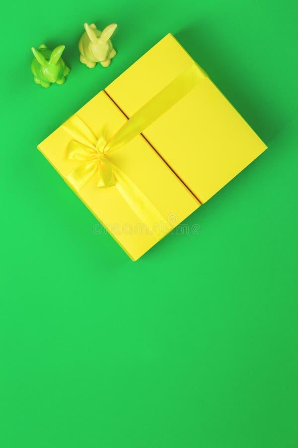 Żółty Easter giftbox z dwa królikami na zielonym tle fotografia royalty free