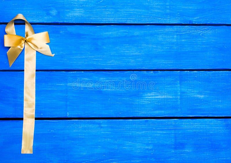 Żółty faborek na błękitnym drewnianym tle, łęk zdjęcie stock
