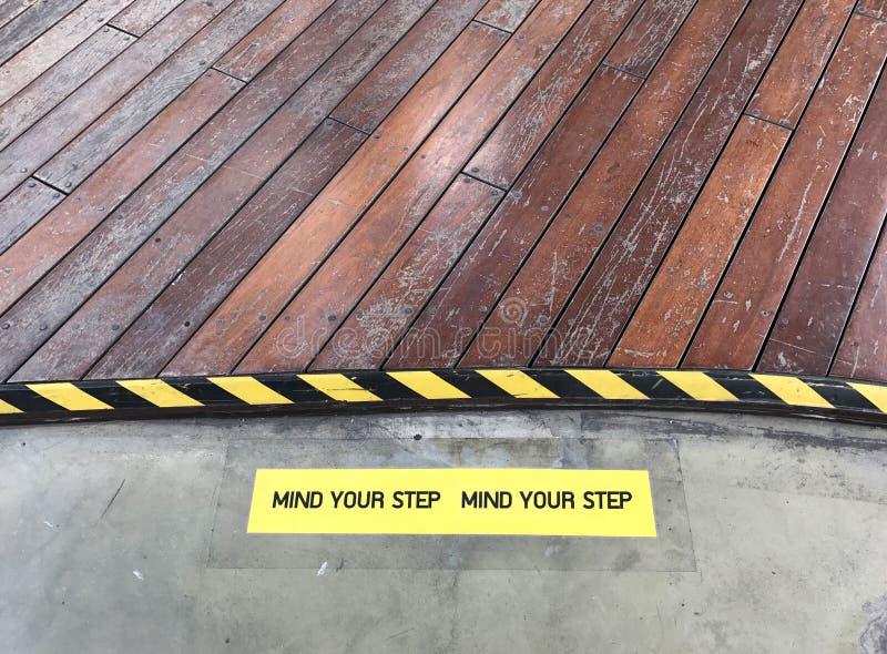 Żółty i czarny znak ostrzegawczy na kroka twierdzić fotografia stock